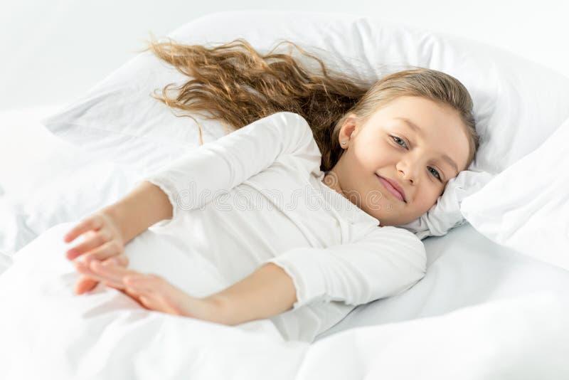 Μικρό κορίτσι στο άσπρο ξύπνημα πιτζαμάτων στο κρεβάτι στο σπίτι στοκ εικόνα με δικαίωμα ελεύθερης χρήσης