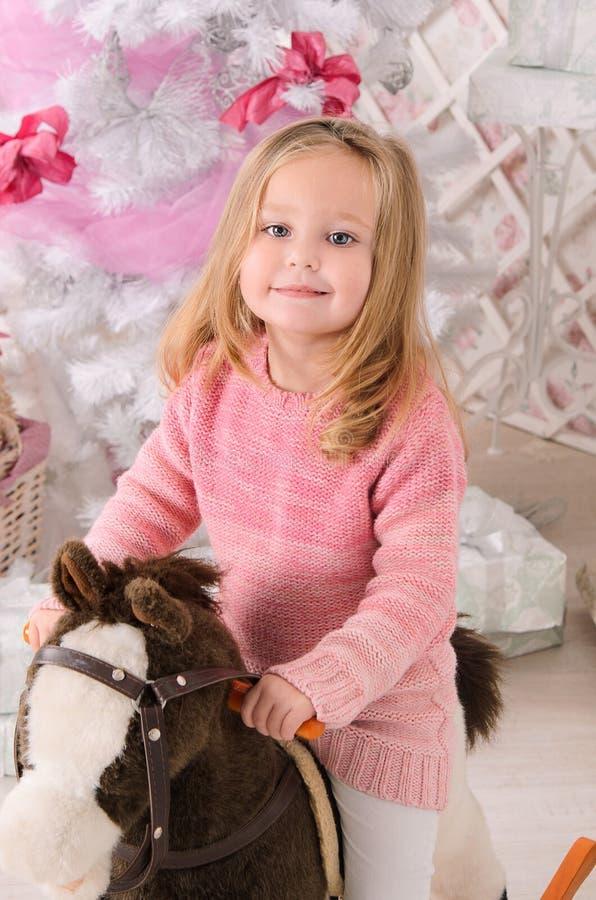 Μικρό κορίτσι στο άλογο παιχνιδιών στο εσωτερικό Χριστουγέννων στοκ εικόνα