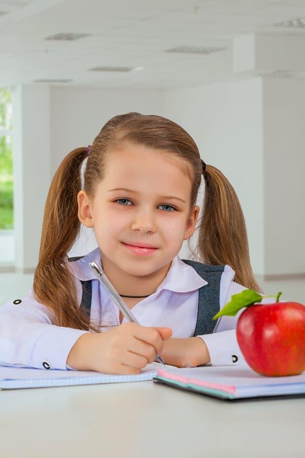 Μικρό κορίτσι στο επιτραπέζιο γράψιμο στοκ φωτογραφίες