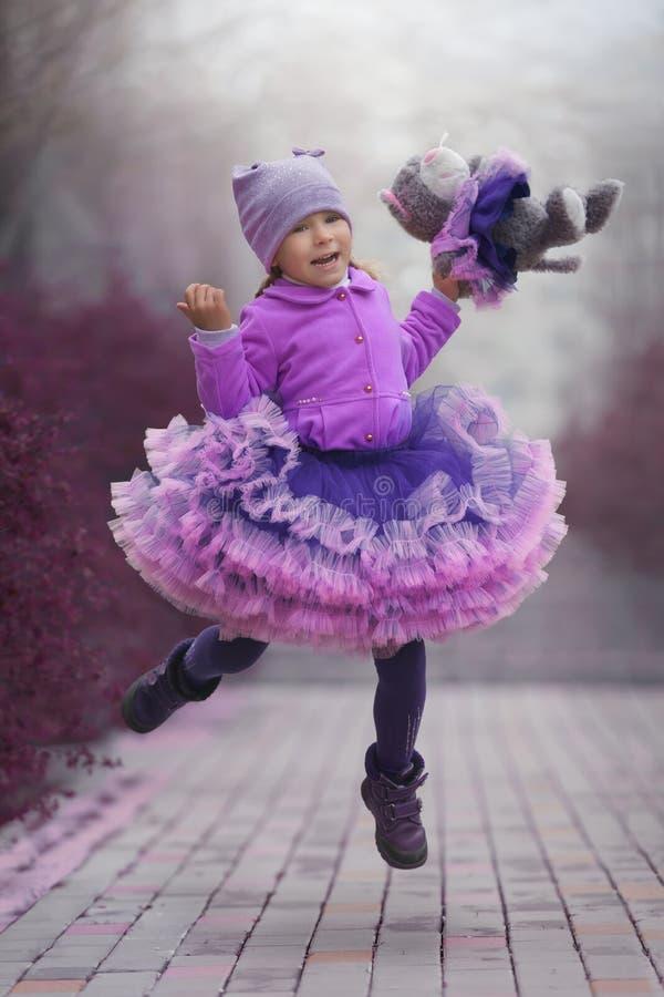 Μικρό κορίτσι στο ιώδες φόρεμα που χορεύει με μια γάτα παιχνιδιών στοκ εικόνα