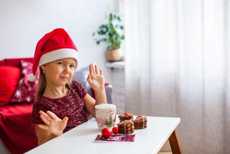Μικρό κορίτσι στο καπέλο Santa με τα μπισκότα πιπεροριζών Χριστουγέννων και το φλυτζάνι του κακάου με marshmallow στοκ φωτογραφία με δικαίωμα ελεύθερης χρήσης