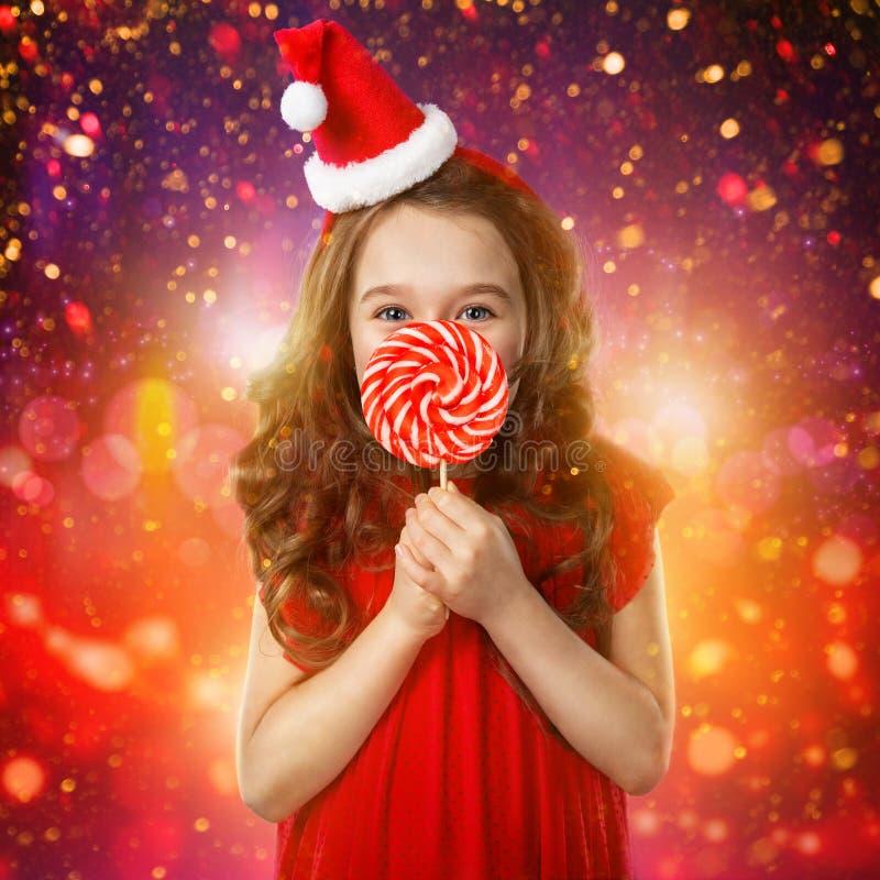 Μικρό κορίτσι στο καπέλο santa με τον κάλαμο καραμελών στενός κόκκινος χρόνος Χριστουγέννων ανασκόπησης επάνω στοκ φωτογραφία
