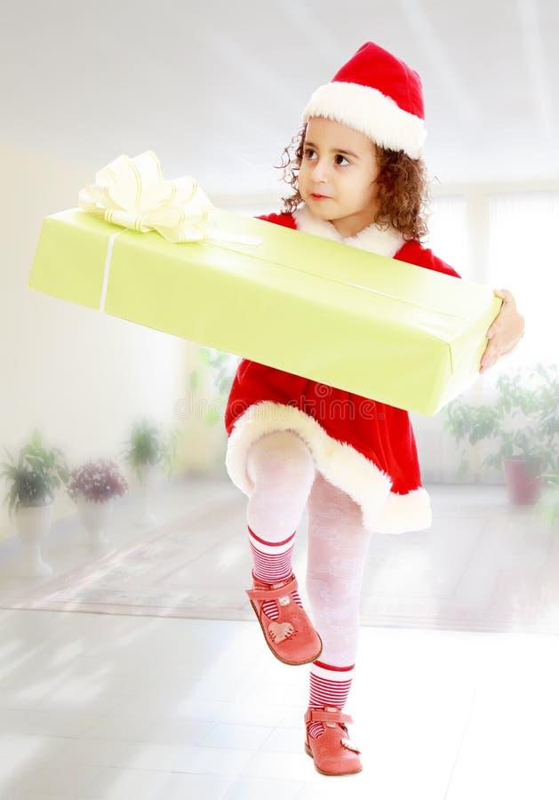 Μικρό κορίτσι στο κοστούμι Άγιου Βασίλη με το δώρο στοκ φωτογραφία με δικαίωμα ελεύθερης χρήσης