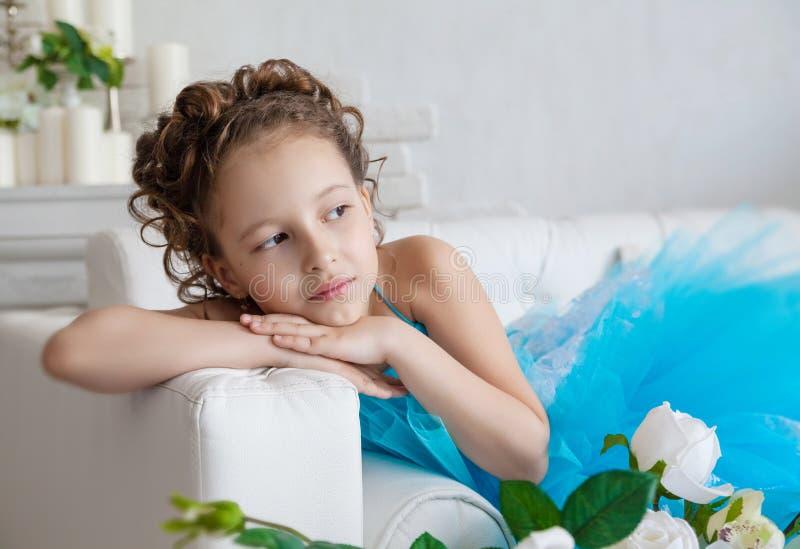 Μικρό κορίτσι στο μπλε φόρεμα που βρίσκεται στον καναπέ στοκ φωτογραφία με δικαίωμα ελεύθερης χρήσης