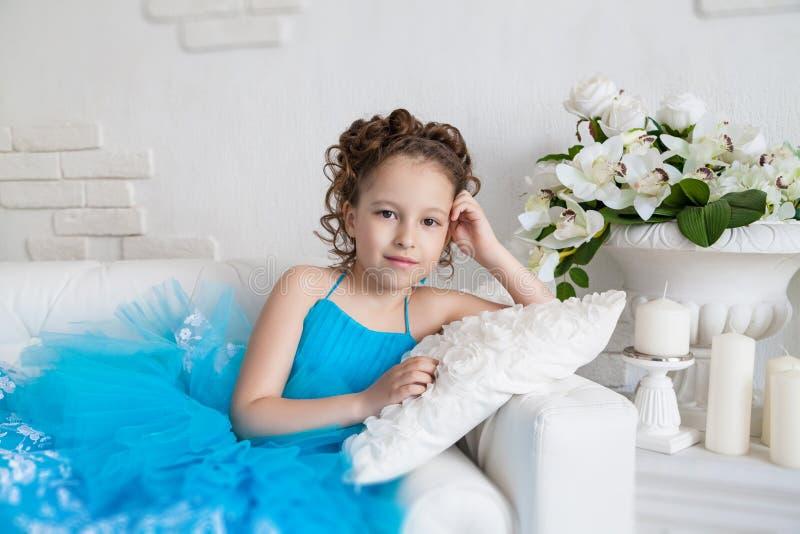 Μικρό κορίτσι στο μπλε φόρεμα που βρίσκεται στον καναπέ στοκ εικόνες