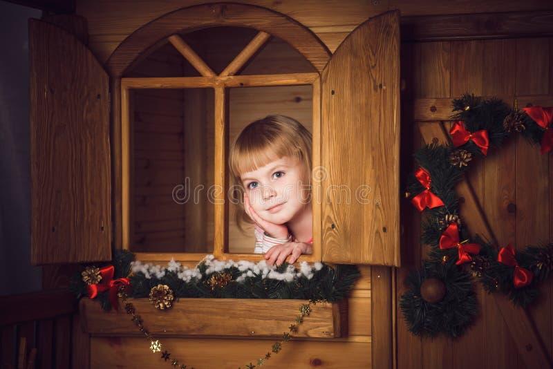 Μικρό κορίτσι στο ξύλινο σπίτι με τη διακόσμηση Χριστουγέννων στοκ εικόνα