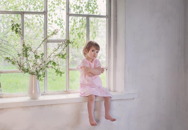 μικρό κορίτσι στο παλαιό windowsill με τα λουλούδια άνοιξη στοκ εικόνα