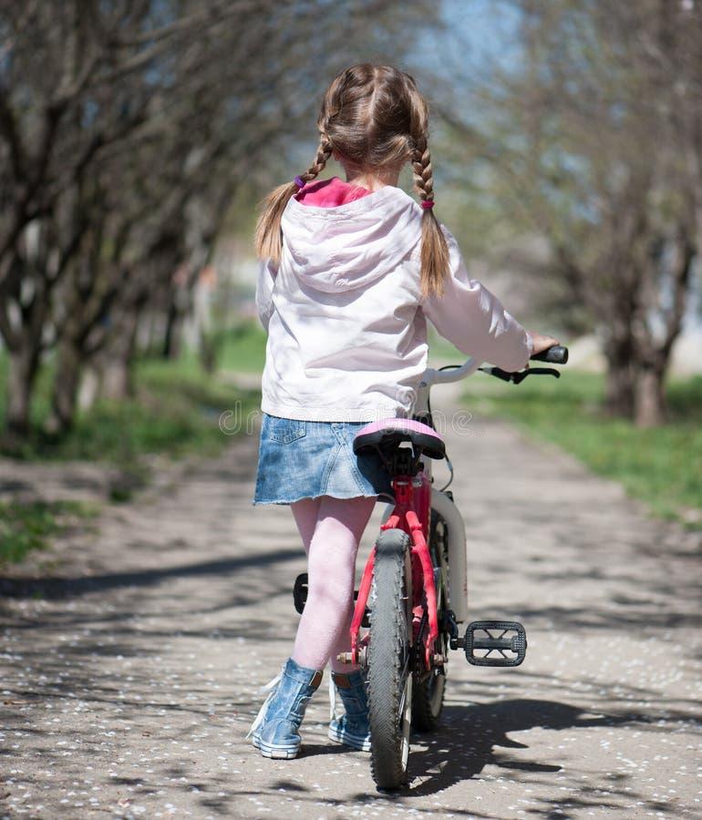 Μικρό κορίτσι στο ποδήλατό της στοκ εικόνα