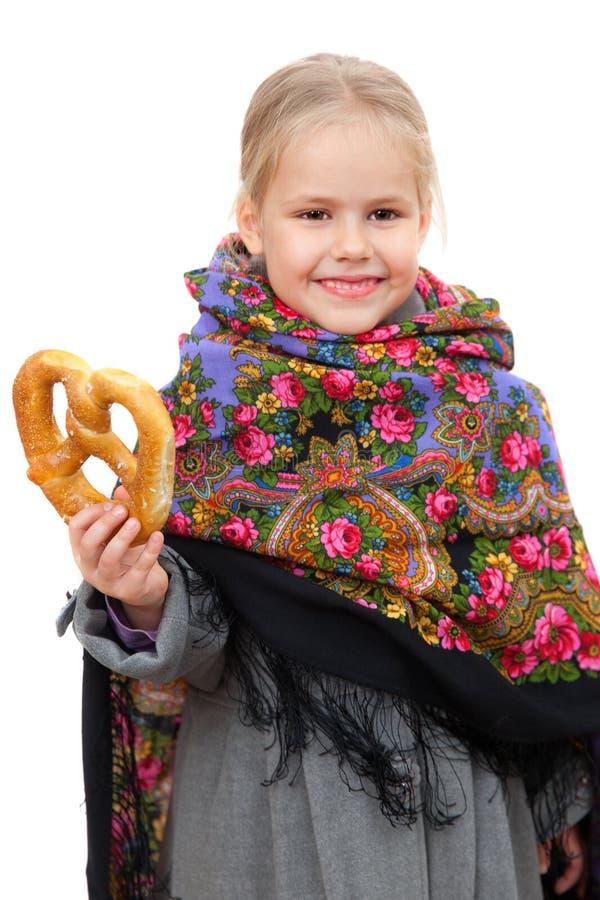 Μικρό κορίτσι στο ρωσικό μαντίλι για το κεφάλι με pretzel στοκ φωτογραφίες