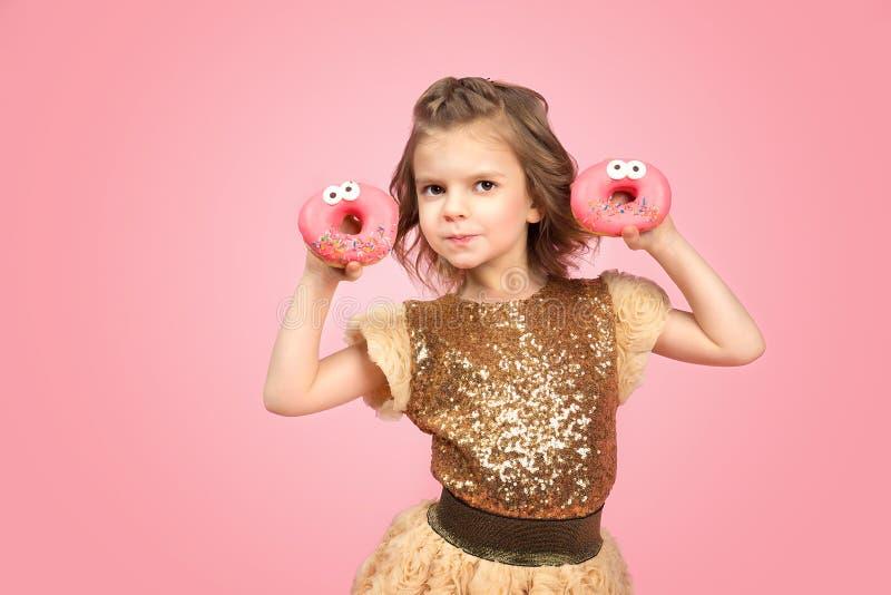 Μικρό κορίτσι στο φόρεμα με τα donuts στοκ εικόνα