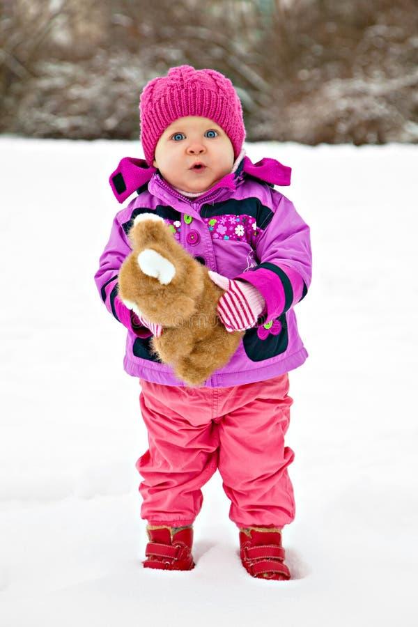 Μικρό κορίτσι στο χιόνι με το παιχνίδι στοκ φωτογραφία με δικαίωμα ελεύθερης χρήσης