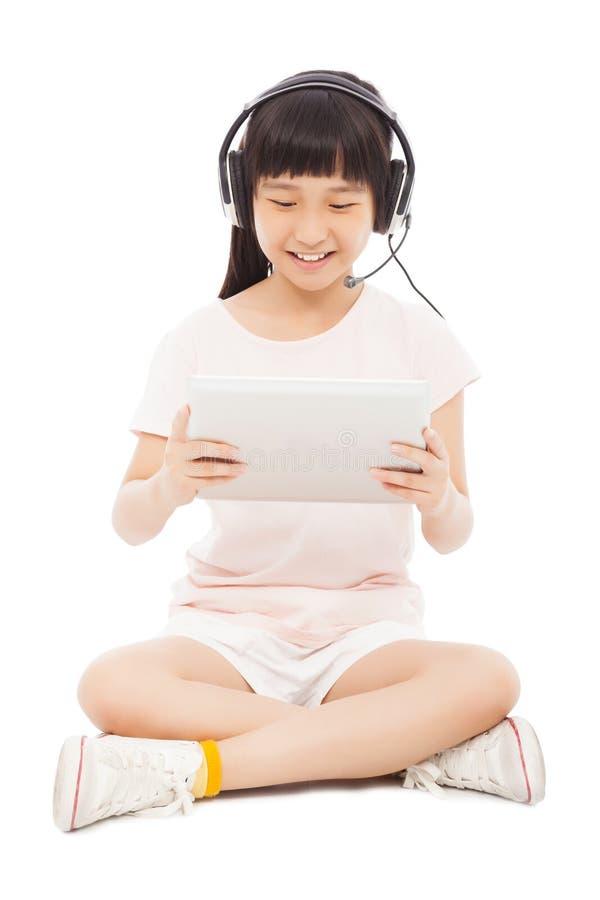 Μικρό κορίτσι συνεδρίασης που κρατά μια ταμπλέτα με το ακουστικό στοκ εικόνες