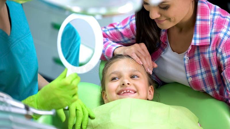 Μικρό κορίτσι της Νίκαιας ευτυχές μετά από τις οδοντικές διαδικασίες, υγιή δόντια θαυμασμού στον καθρέφτη στοκ εικόνες