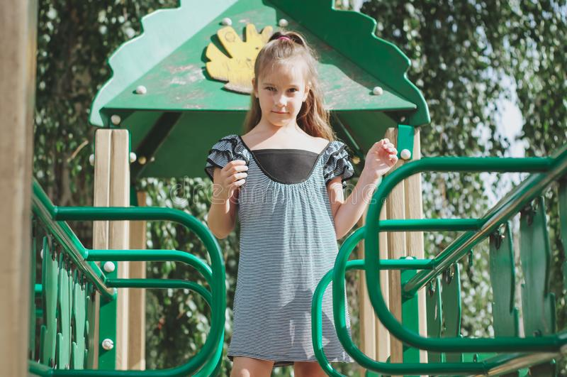 μικρό κορίτσι τη θερινή ηλιόλουστη ημέρα παιδικών χαρών στοκ εικόνα