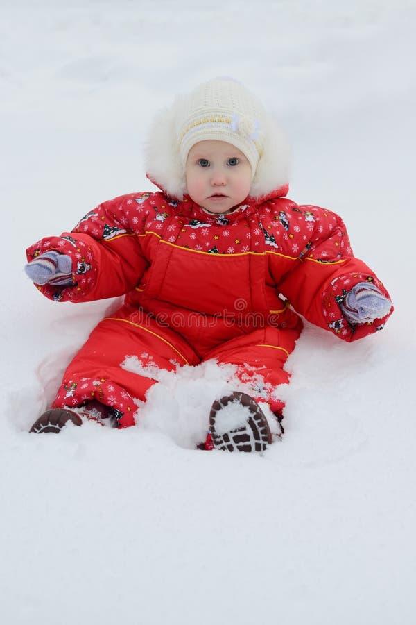 μικρό κορίτσι το χειμώνα jumpsuit που εκπλήσσεται snowdrift στοκ φωτογραφίες