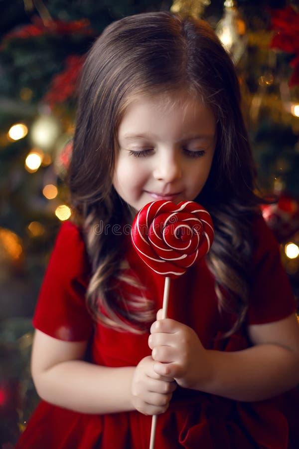 Μικρό κορίτσι τρία έτη γλειψίματα στα κόκκινα φορεμάτων στοκ εικόνα με δικαίωμα ελεύθερης χρήσης
