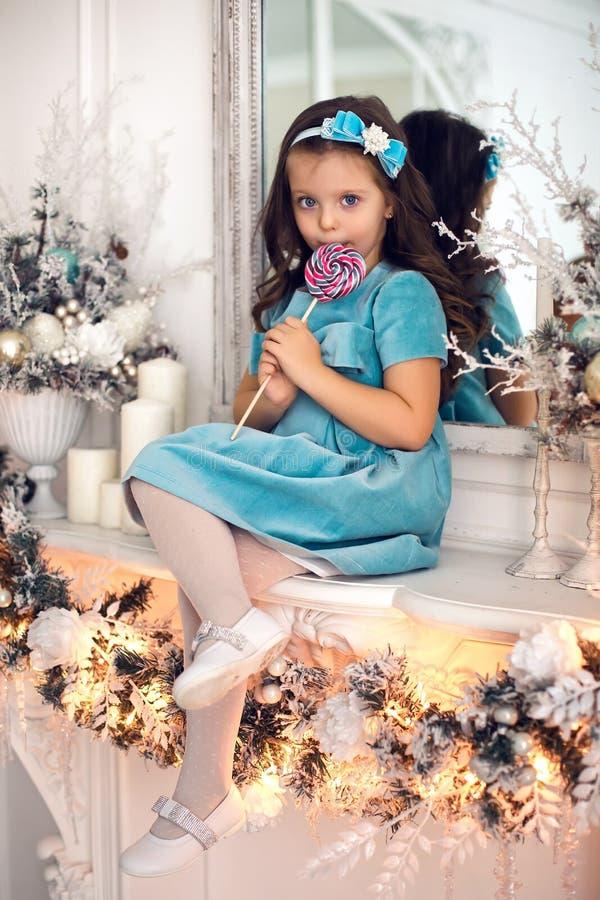 Μικρό κορίτσι τρία έτη γλειψίματα στα μπλε φορεμάτων στοκ φωτογραφία με δικαίωμα ελεύθερης χρήσης