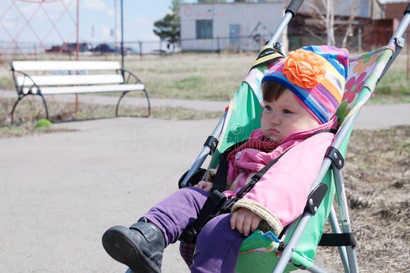 Μικρό κορίτσι υπαίθριο στον περιπατητή, που περπατά με το μωρό στη με λάθη, μεταφορά μωρών που χρησιμοποιεί για το παιδί, εκμετάλ στοκ φωτογραφία με δικαίωμα ελεύθερης χρήσης