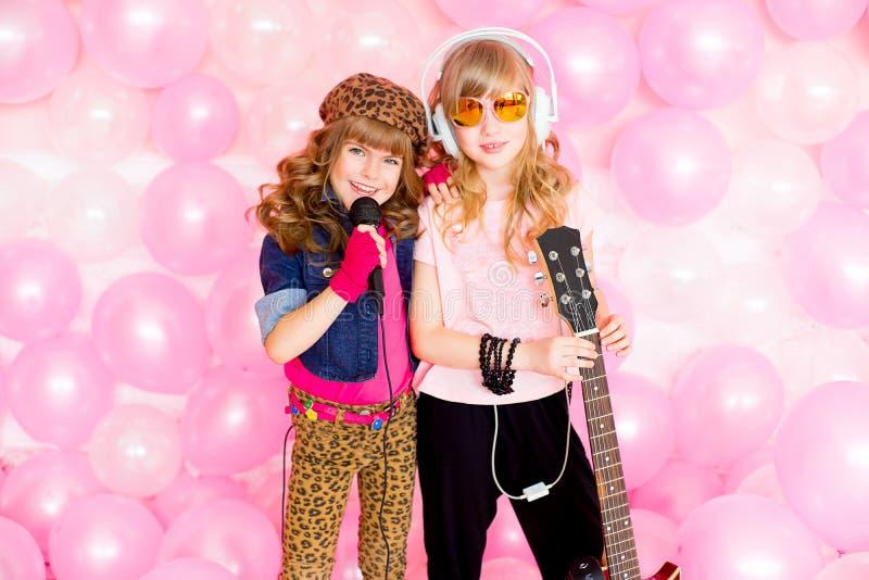 Μικρό κορίτσι δύο με ένα μικρόφωνο στοκ εικόνα με δικαίωμα ελεύθερης χρήσης