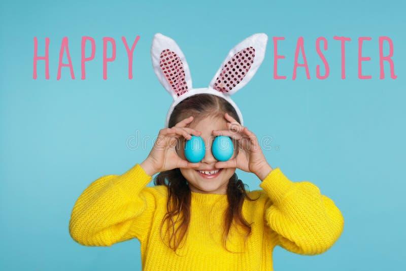 Μικρό κορίτσι headband αυτιών λαγουδάκι στα αυγά Πάσχας εκμετάλλευσης κοντά στα μάτια απεικόνιση αποθεμάτων