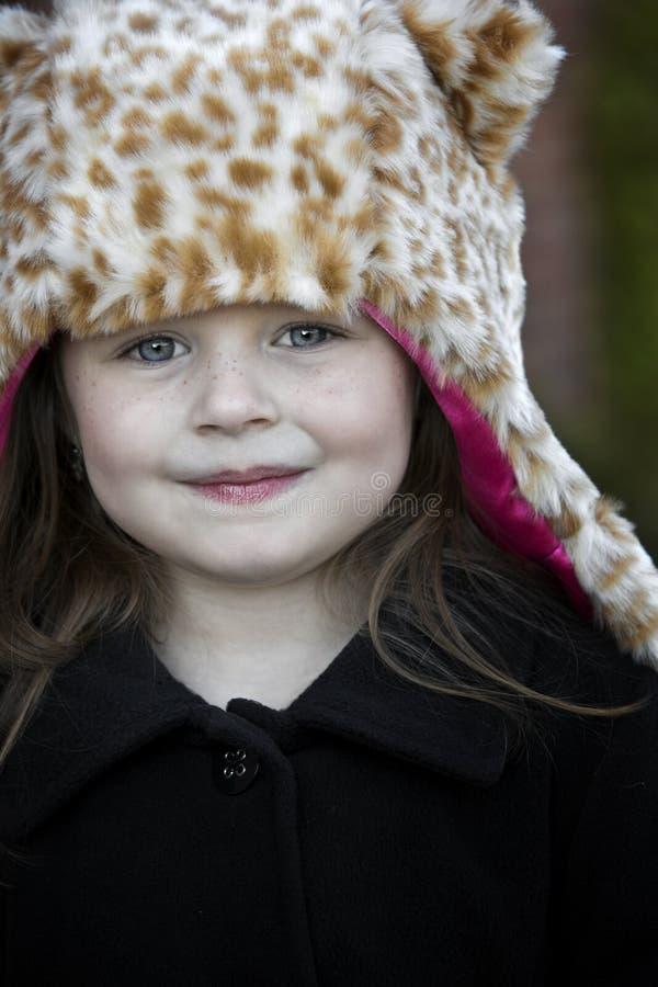 Μικρό κορίτσι leopard στο πλαστό καπέλο γουνών στοκ φωτογραφία