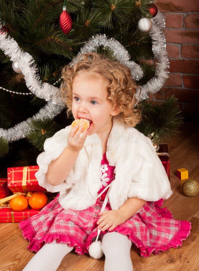 Μικρό κορίτσι Preaty που τρώει tangerine στοκ εικόνες