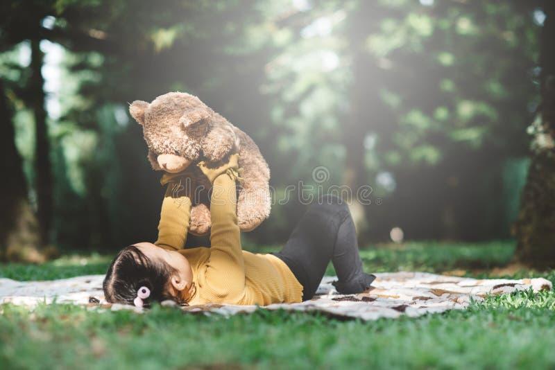 Μικρό κοριτσάκι που πετάει το αρκουδάκι της στοκ φωτογραφία