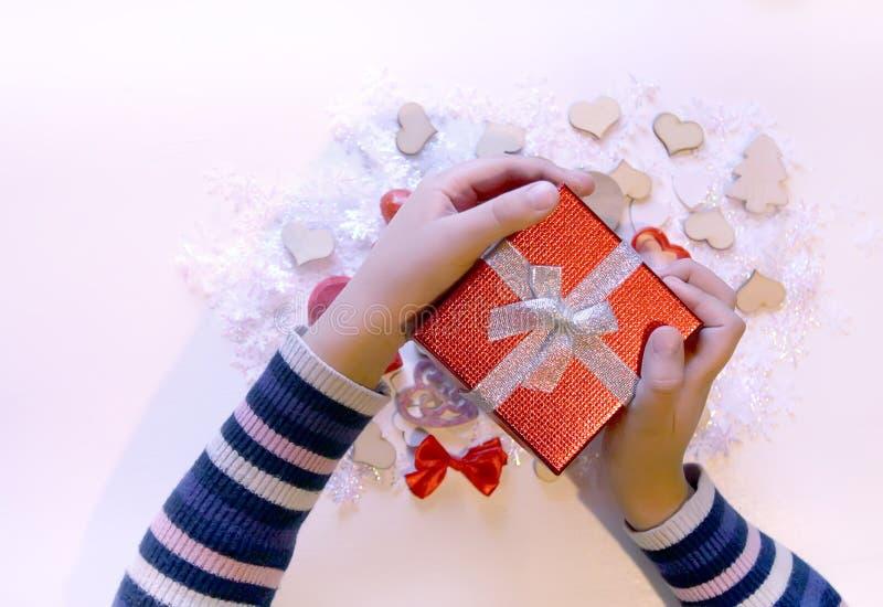Μικρό κόκκινο κιβώτιο δώρων στο child& x27 χέρια του s Χριστούγεννα και ντεκόρ NewYear στοκ εικόνες με δικαίωμα ελεύθερης χρήσης