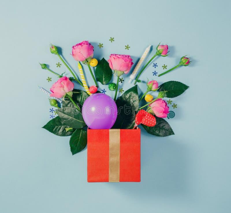 Μικρό κόκκινο κιβώτιο δώρων με τα τριαντάφυλλα, το μπαλόνι, το κομφετί και τα κεριά στοκ εικόνες