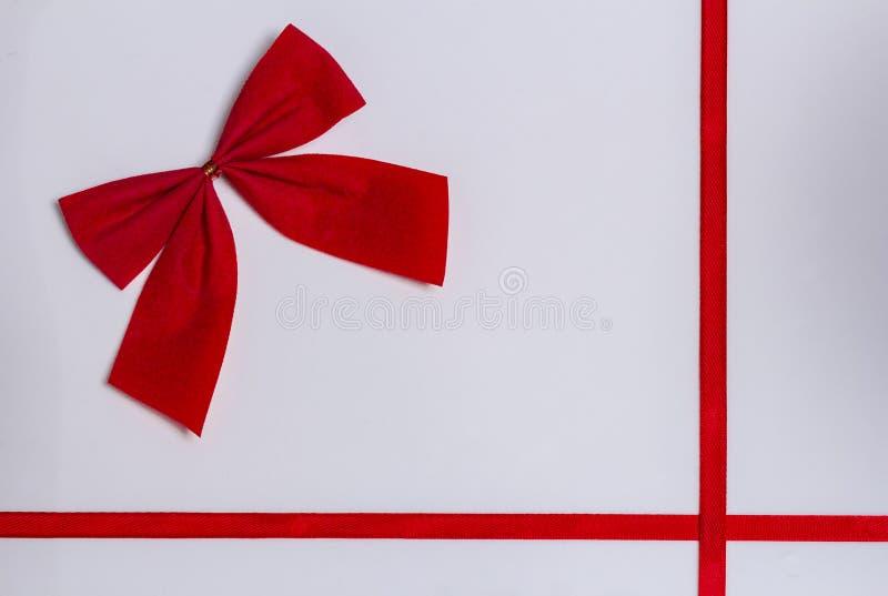 μικρό κόκκινο τόξο σε ένα άσπρο υπόβαθρο με τις κόκκινες κορδέλλες στοκ φωτογραφίες