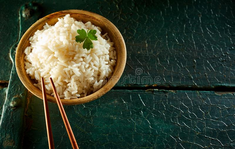 Μικρό κύπελλο του άσπρου ρυζιού με Chopsticks στον πίνακα στοκ εικόνες