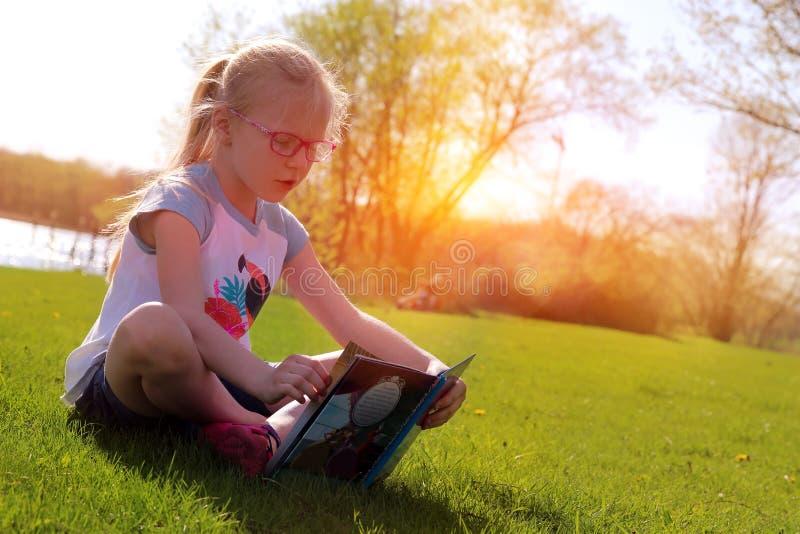 Μικρό ξανθό καλαμώνοντας βιβλίο κοριτσιών έξω στοκ φωτογραφίες