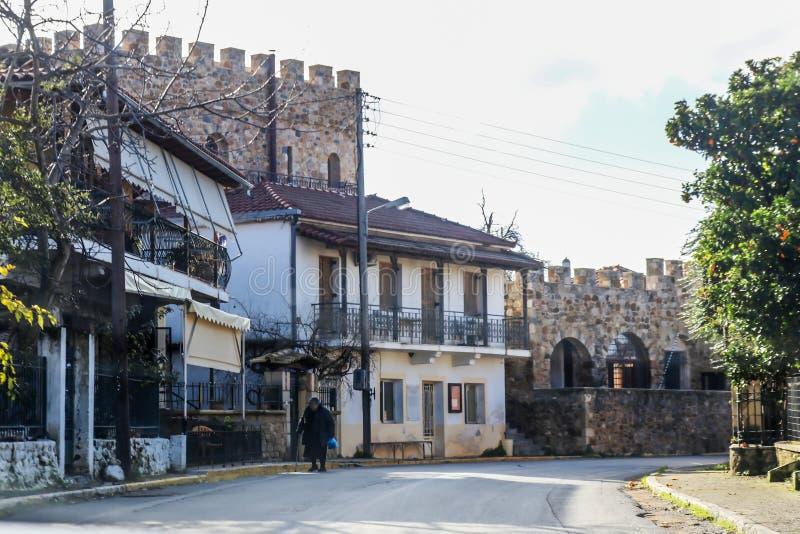 Μικρό ορεινό χωριό που χτίζεται ενάντια στο κάστρο όπως τους τοίχους με το ηλικιωμένο άτομο που περπατά κατά μήκος του πεζοδρομίο στοκ φωτογραφίες