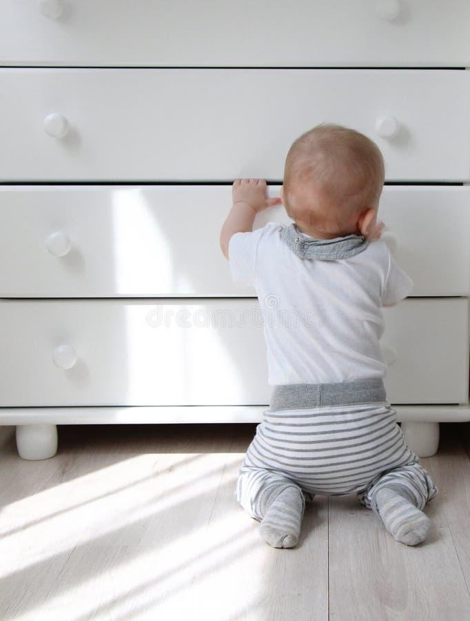 Μικρό παιδί και ένα ντουλάπι στοκ φωτογραφίες