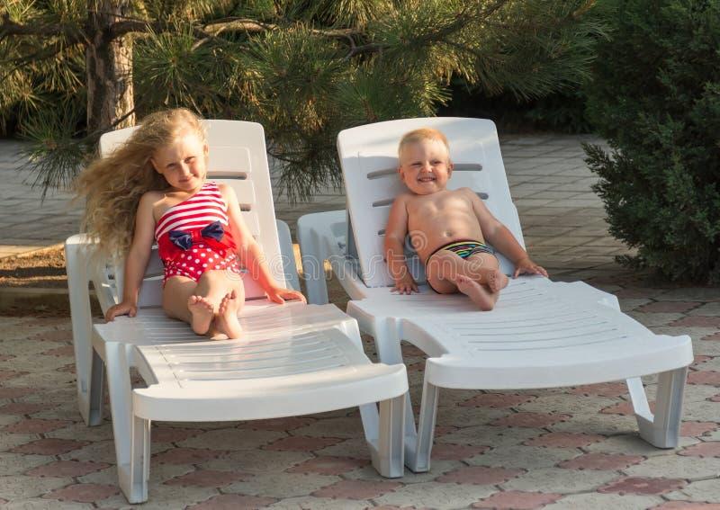 Μικρό παιδί και κορίτσι με την πολυτελή τρίχα στην καρέκλα σαλονιών, στο υπόβαθρο φύσης στοκ φωτογραφίες