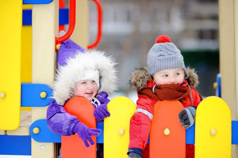 Μικρό παιδί και κορίτσι στα χειμερινά ενδύματα που έχουν τη διασκέδαση υπαίθρια στην παιδική χαρά στοκ εικόνα