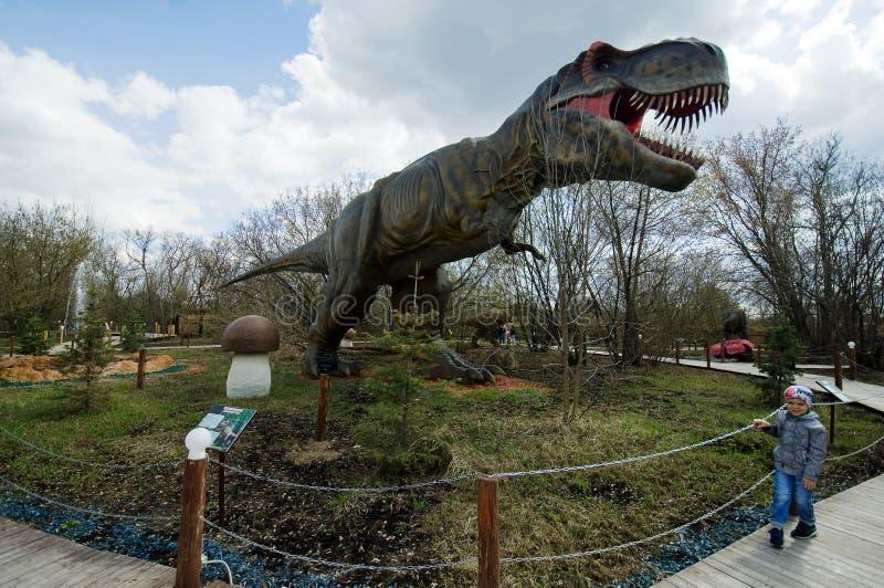Μικρό παιδί κοντά στο Tyrannosaur Rex στο πάρκο δεινοσαύρων, Μόσχα, RU στοκ εικόνες