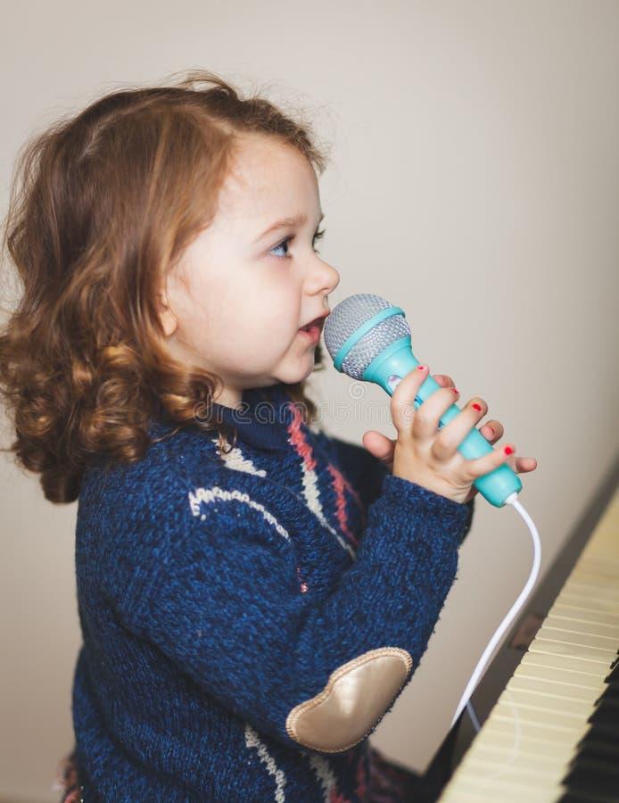 Μικρό παιδί κοριτσιών, πιάνο και μικρόφωνο παιχνιδιών στοκ εικόνες