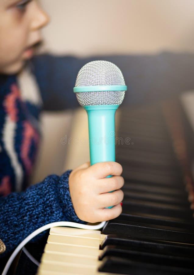 Μικρό παιδί κοριτσιών, πιάνο και μικρόφωνο παιχνιδιών στοκ εικόνα