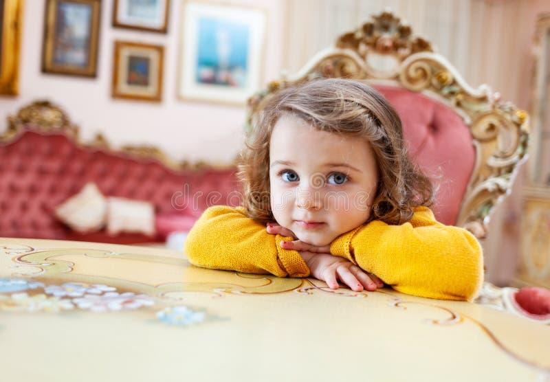 Μικρό παιδί κοριτσιών σε ένα καθιστικό με το μπαρόκ ντεκόρ στοκ φωτογραφία