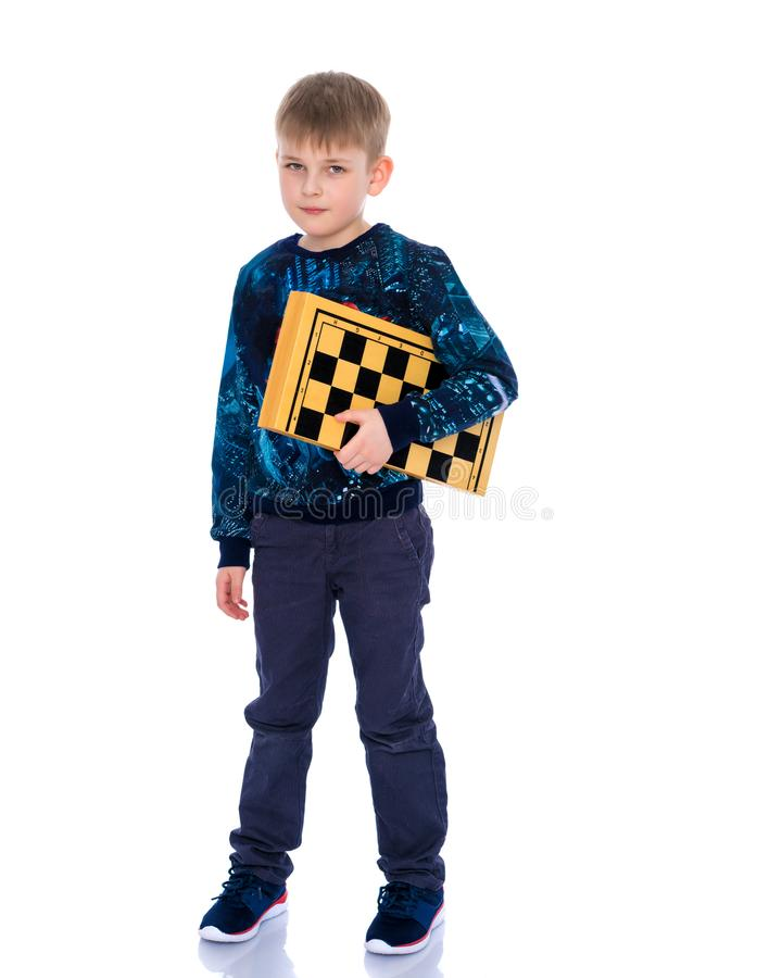 Μικρό παιδί με μια σκακιέρα στοκ εικόνες