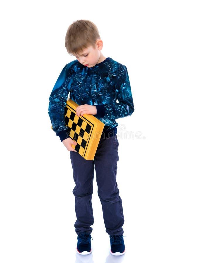 Μικρό παιδί με μια σκακιέρα στοκ φωτογραφία με δικαίωμα ελεύθερης χρήσης