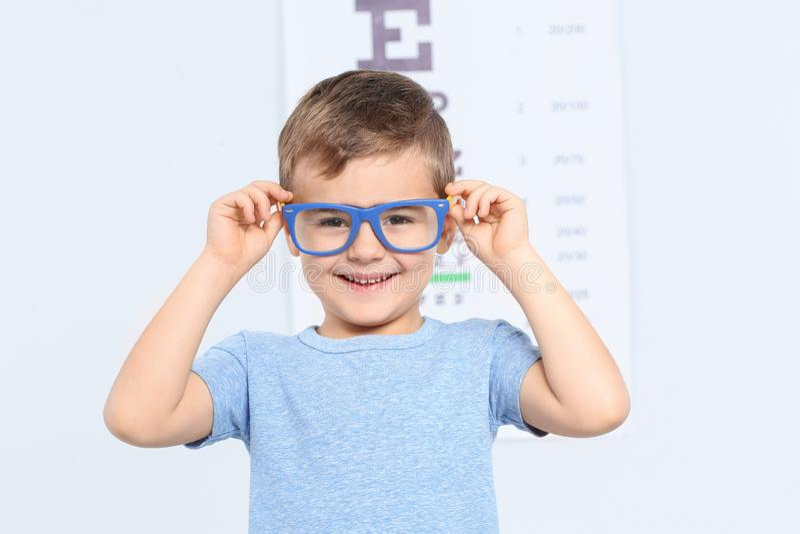 Μικρό παιδί με τα γυαλιά που επισκέπτεται το γιατρό των παιδιών στην κλινική, διάστημα για το κείμενο στοκ εικόνες