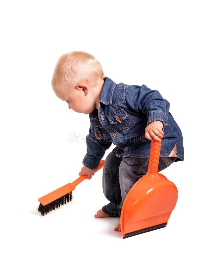 Μικρό παιδί με τη σκούπα και dustpan στοκ φωτογραφίες