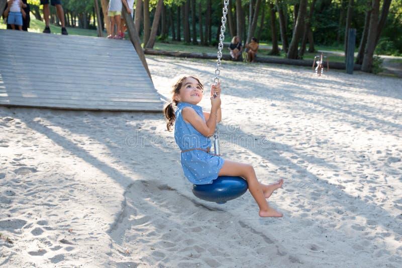 Μικρό παιδί μικρών κοριτσιών που έχει τη διασκέδαση στη γραμμή φερμουάρ παιδικών χαρών στο πάρκο πόλεων στοκ εικόνα