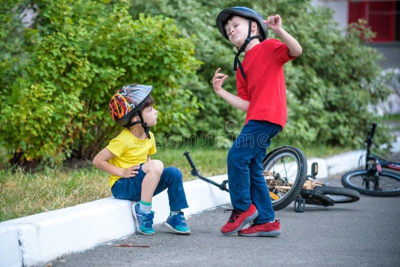 Μικρό παιδί πεσμένος μακριά του ποδηλάτου του Δυστυχισμένη συνεδρίαση αγοριών στην άσφαλτο που φαίνεται το γόνατό του Ο φίλος του στοκ εικόνα με δικαίωμα ελεύθερης χρήσης