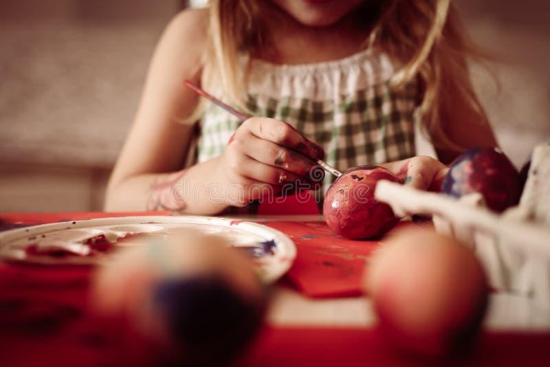 Μικρό παιδί που έχει τη διασκέδαση που χρωματίζει τα αυγά Πάσχας στοκ φωτογραφίες