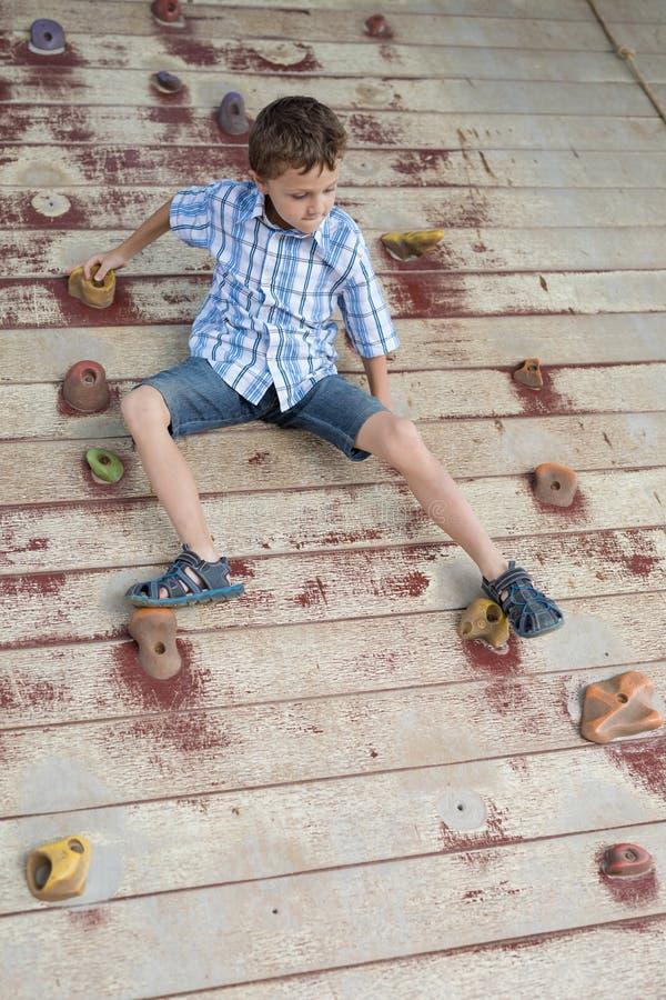 Μικρό παιδί που αναρριχείται σε έναν τοίχο βράχου υπαίθριο στοκ φωτογραφίες