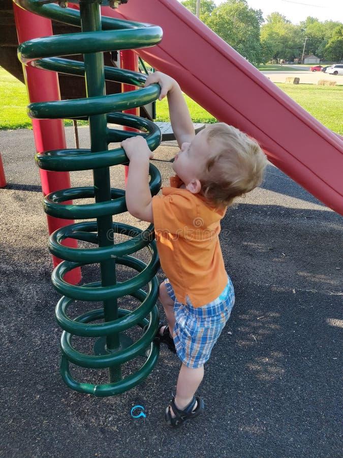 Μικρό παιδί που αναρριχείται στον εξοπλισμό παιδικών χαρών στοκ εικόνες