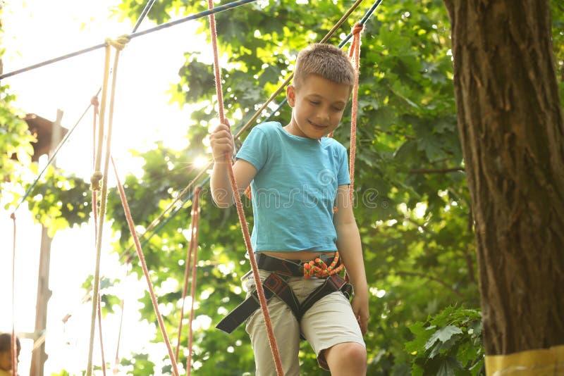 Μικρό παιδί που αναρριχείται στο πάρκο περιπέτειας στοκ φωτογραφίες